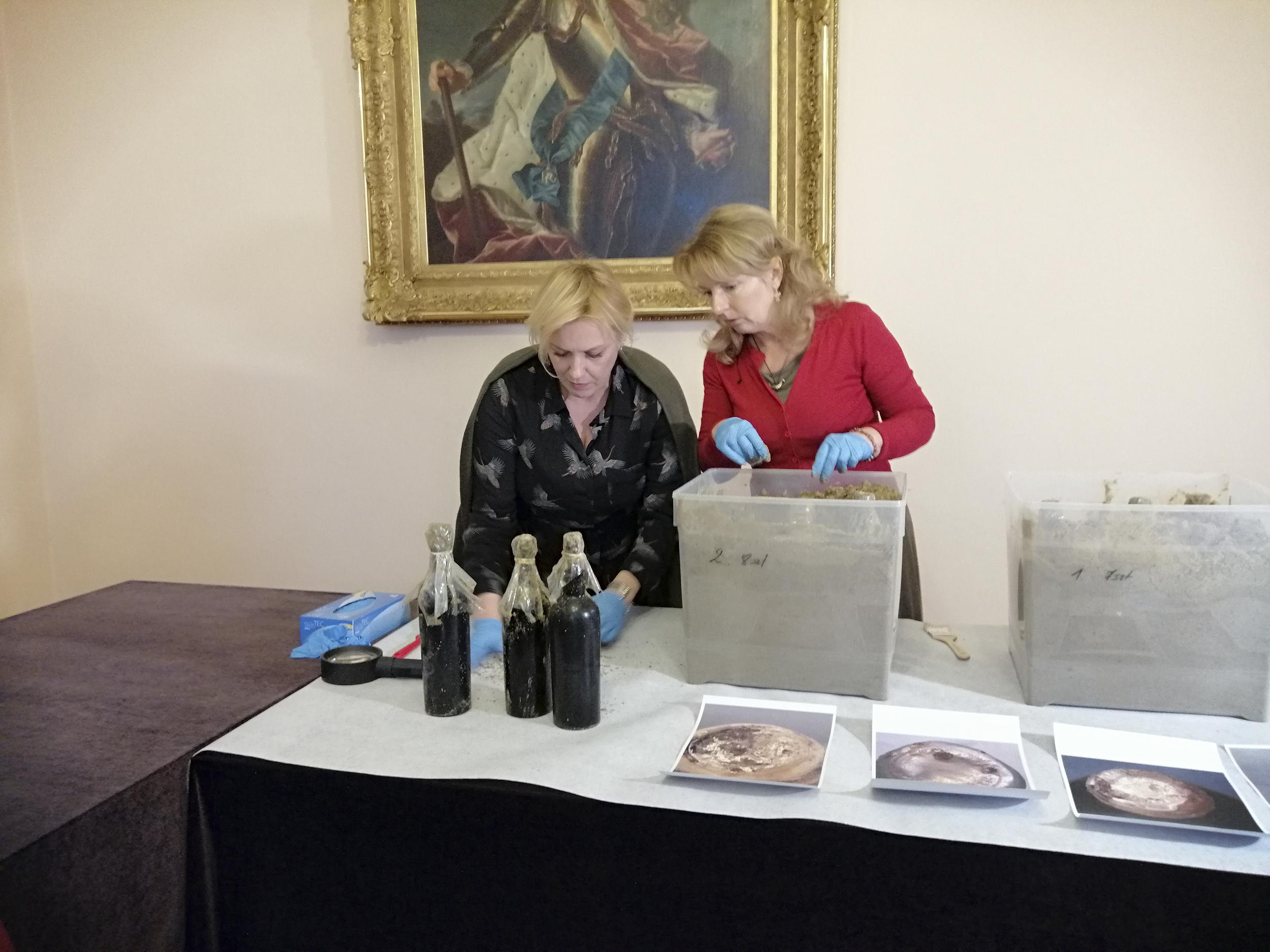 Fotografia. Dwie kobiety w lateksowych rękawiczkach nachylające się nad stołem. Przed nimi ustawione pojemniki z piachem i trzy zakurzone butelki z winem.