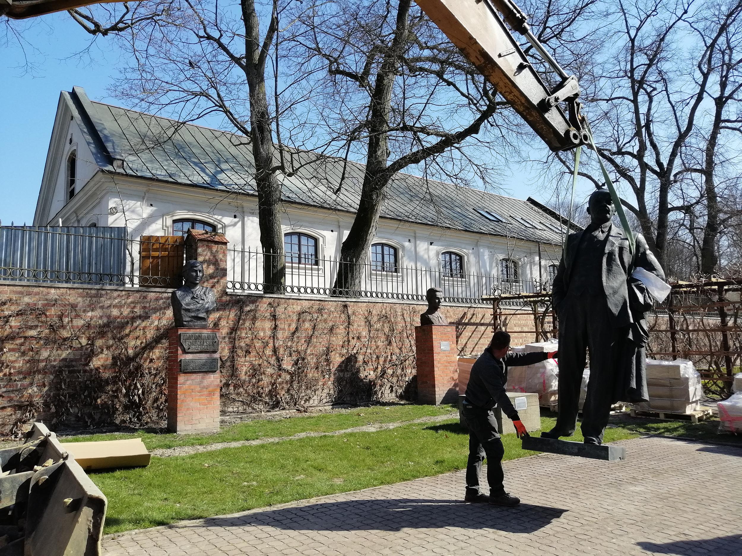 Fotografia. Pomnik Włodzimierza Lenina, postać całościowa. Rzeźba z brązu o wymiarach 260 x 120 x 75 cm uniesiona nad ziemię za pomocą pasów holowniczych. Po lewej stronie mężczyzna podtrzymujący rzeźbę.