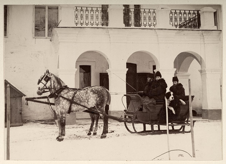 Pozioma, czarno-biała fotografia przedstawiająca trzech mężczyzn w średnim wieku, siedzących w saniach, zaprzężonych w dwa szare konie w jaśniejsze plamki. Na przodzie sań dwaj mężczyźni ubrani w kożuchy i zimowe czapki. Jeden z nich trzyma w ręku bat. Z tyłu mężczyzna ubrany podobnie,  spogląda w stronę fotografa. Na kolanach trzyma olbrzymiego psa rasy bernardyn. W tle budynek z jasną elewacją i czterokolumnowym portykiem przed wejściem. U góry widoczny fragment tarasu i okna pierwszego piętra.