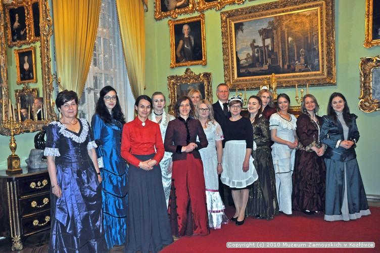 Fotografia. Grupa trzynastu kobiet i mężczyzny ubranych w stylizowane stroje z końca XIX wieku, na tle pomieszczenia malowanego na jasno zielony kolor. Ściany zdobi lustro i obrazy oprawione w bogato rzeźbione i złocone ramy.