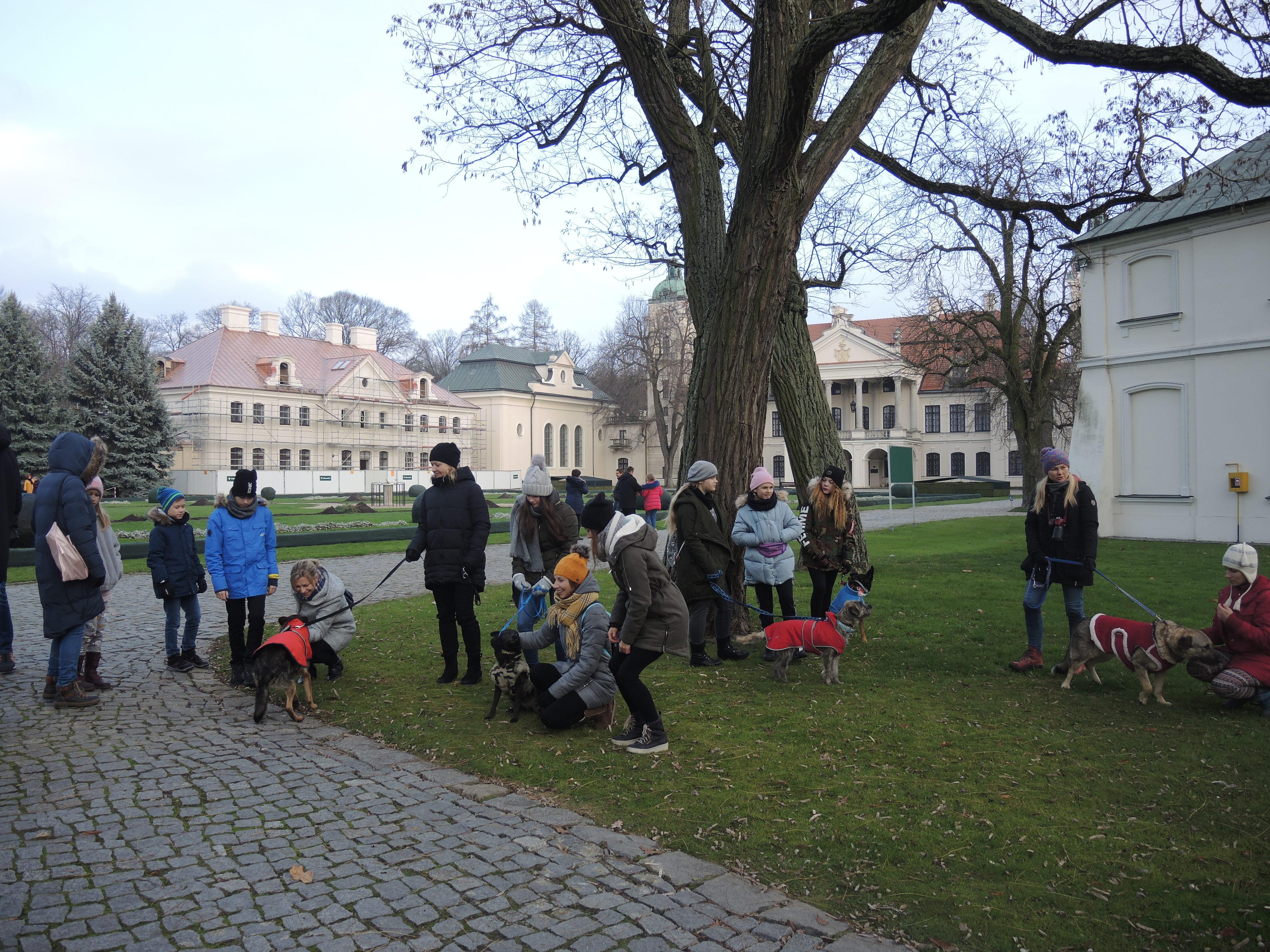 Fotografia. Grupa stojących ludzi w kolorowych ciepłych kurtkach i czapkach, pogrupowana po kilka osób. Niektóre osoby przykucnięte. Rozmawiają, śmieją się. Towarzyszą im cztery psy na smyczach ubrane w kolorowe kubraczki. W tle okazała dwukondygnacyjna rezydencja z portykiem i czerwonym dwuspadowym dachem oraz pobocznymi budynkami.