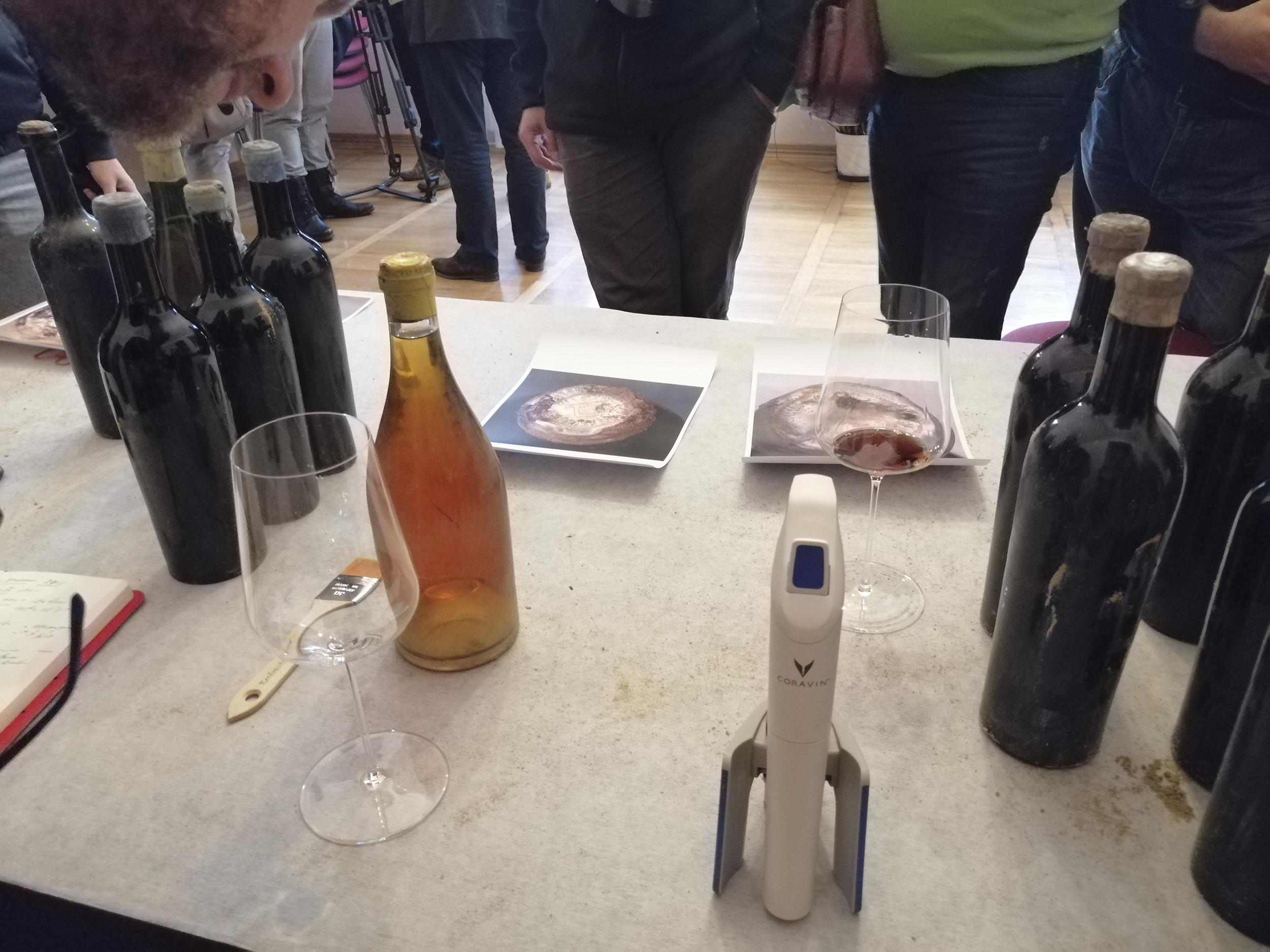 Fotografia. Na pierwszym planie urządzenie służące do nalewania wina bez konieczności wyciągani korka. Obok szklany kieliszek i wino w butelce z jasnego szkła. W tle oszronione butelki z winem z ciemnego szkła.