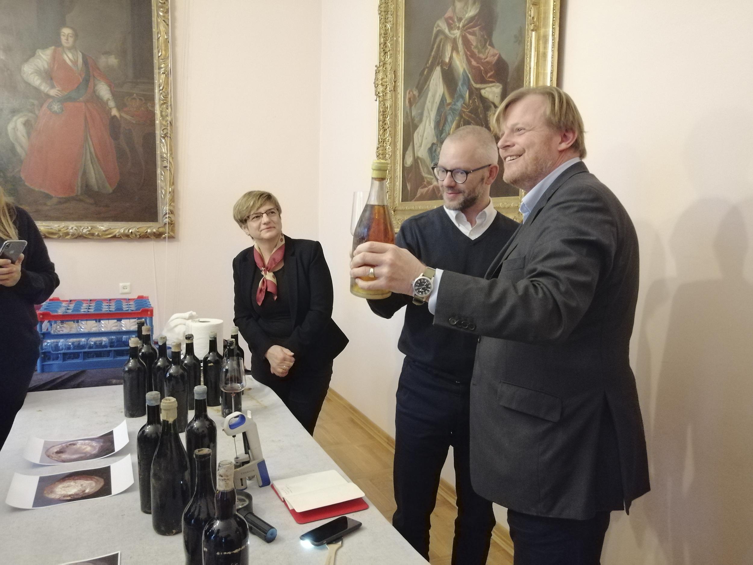 Fotografia. Dwaj mężczyźni widoczni z lewego profilu. Jeden trzyma wysoko uniesiona butelkę z jasnego szkła, drugi kieliszek z próbką wina. W tle uśmiechnięta kobieta w apaszce na szyi.
