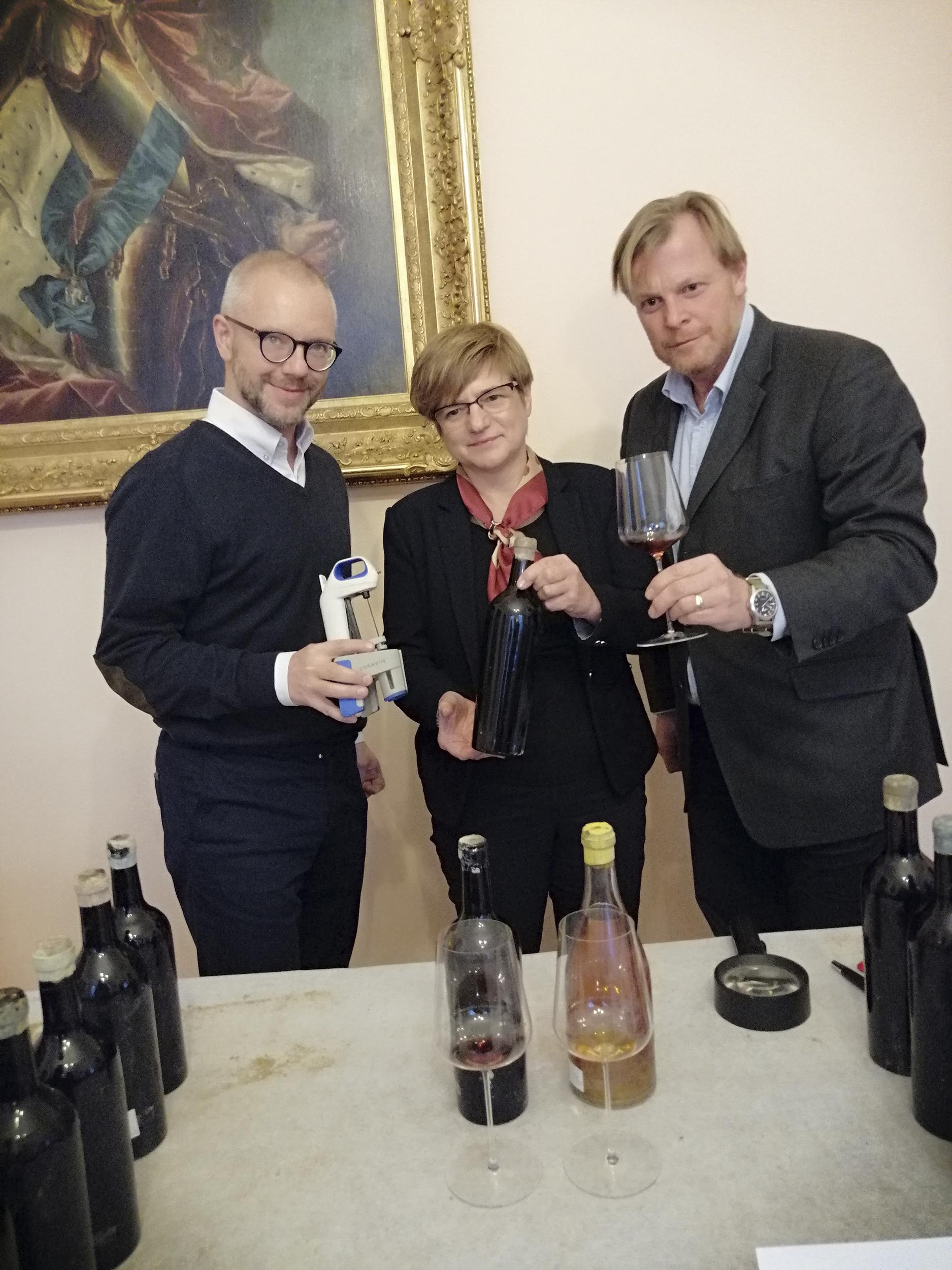 Fotografia. Dwaj mężczyźni i stojąca pomiędzy nimi kobieta, uśmiechnięci patrzą w stronę fotografa. Mężczyzna po lewej trzyma urządzenie służące do nalewania wina bez konieczności wyciągani korka, kobieta butelkę z ciemnego szkła, mężczyzna po prawej kieliszek z próbką wina.