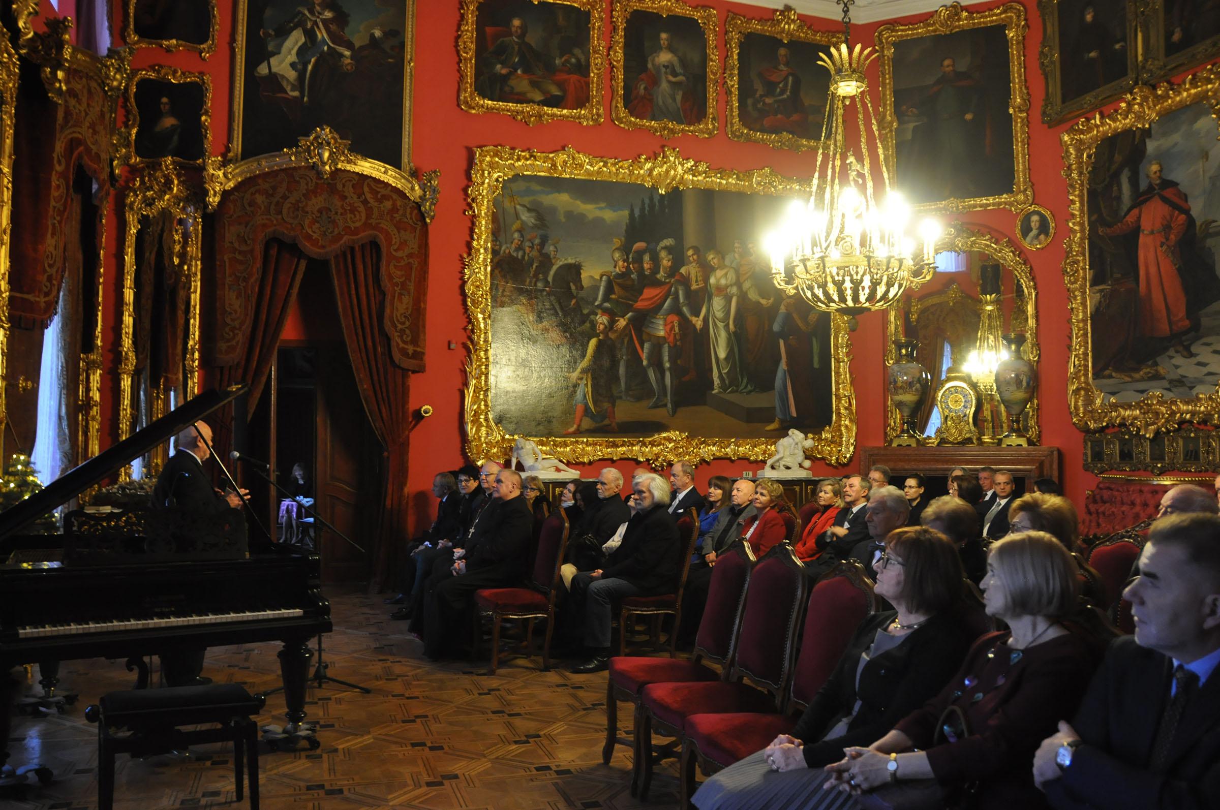 Fotografia. Duże pomieszczenie pomalowane na czerwono, nastrojowo oświetlone. Na ścianach w bogato rzeźbionych i złoconych ramach wiszą w równych odległościach obrazy. Po prawej stronie na obitych bordowym aksamitem krzesłach siedzą zasłuchani ludzie. Po lewej stronie otwarty fortepian a za nim mówiący do mikrofonu starszy mężczyzna.