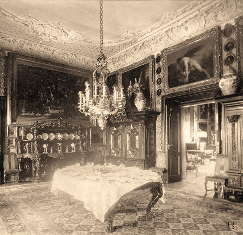 Jadalnia, fotografia archiwalna Czarno-biała, pozioma fotografia. Bogato urządzone wnętrze pałacowej jadalni. Na pierwszym planie ustawiony na środku pomieszczenia ciemny, barokowy stół z nogami zakończonymi łapami lwa, nakryty białym obrusem. Na nim rozłożona zastawa stołowa. Nad stołem okazały, wieloramienny świecznik. W głębi pod ścianą bogato rzeźbiony, ciężki dwupółkowy bufet, na którym ułożono ozdobne talerze i wazki. Pod ścianą po prawej stronie olbrzymie gdańskie szafy, na których ustawiono duże, dalekowschodnie wazy. Pomiędzy nimi otwarte przejście do drugiego salonu. Ciemne ściany wypełniają szczelnie obrazy różnej wielkości i kształtu ubrane w bogato zdobione i złocone rany. Biały sufit pokrywają misterne sztukaterie. Na podłodze dywan w geometryczne wzory zakrywający niemal cały parkiet.