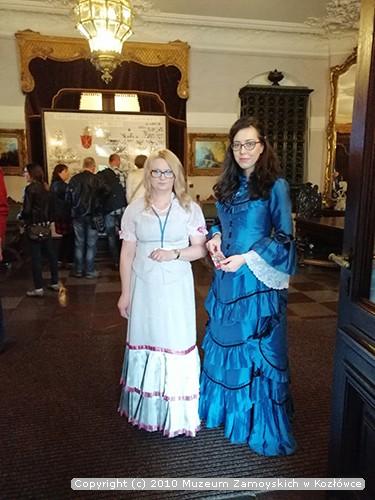 Fotografia. Dwie kobiety w okularach ubrane w stylizowane dziewiętnastowieczne suknie, pozują do zdjęcia. W tle grupa osób przygląda się, umieszczonemu na tablicy, drzewu genealogicznemu.